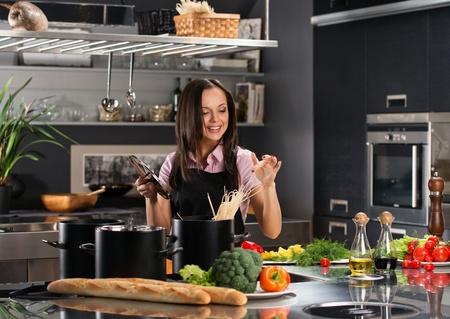 モダンなキッチンにスパゲティを調理する若い女性を笑顔