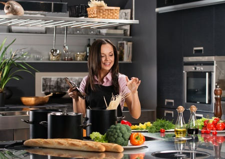 Smiling young woman cooking spaghetti on a modern kitchen