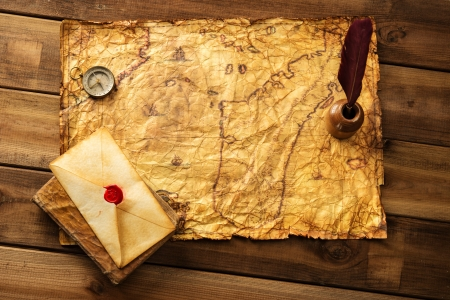 Quill pen, compass and envelope on old map over wooden
