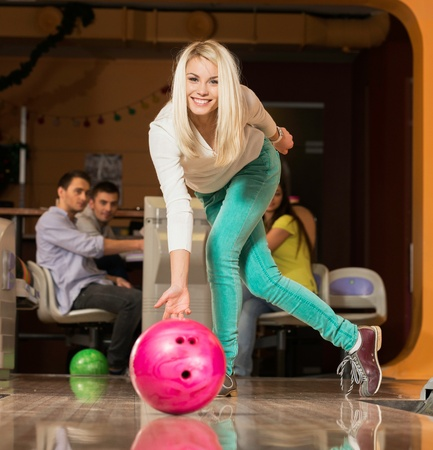 Mensen kijken jonge blonde vrouw gooien bowlingbal Stockfoto