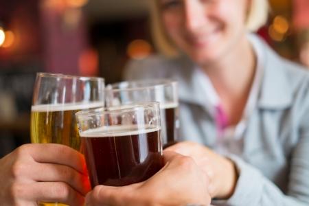 Mensen met bier roosteren in een pub Stockfoto