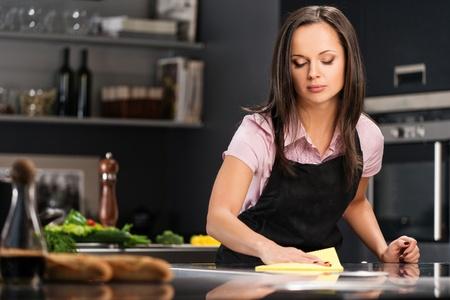 Mujer alegre joven que limpia la cocina moderna