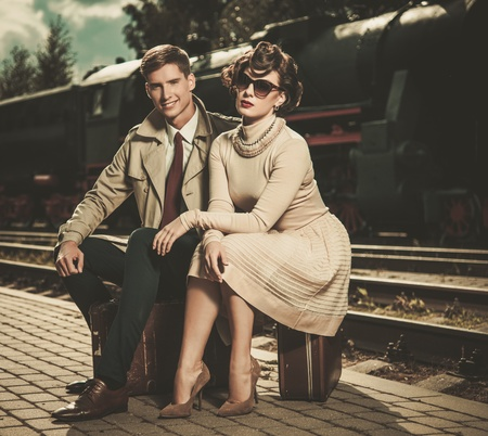 Beautiful vintage style couple sitting on suitcases on  train station platform
