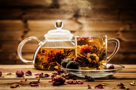 Theepot en glazen beker met bloeiende thee binnen bloem tegen houten achtergrond