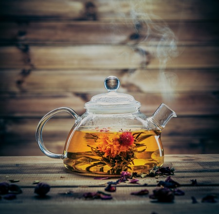 Glass teapot with blooming tea flower inside against wooden background