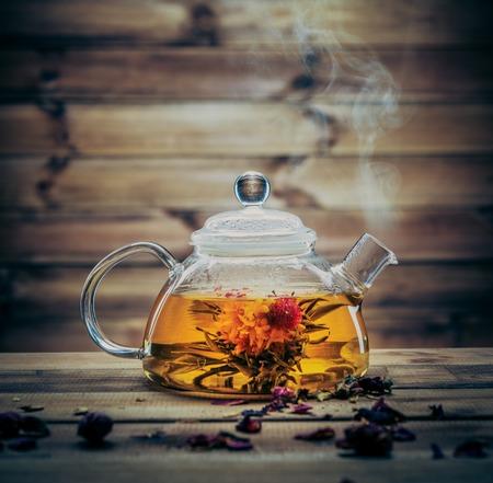 Glazen theepot met bloeiende thee binnen bloem tegen houten achtergrond Stockfoto
