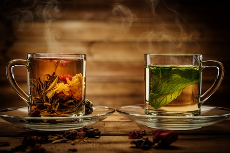 Zwei Glasschalen mit Tee Blume und Pfefferminztee gegen Holzuntergrund