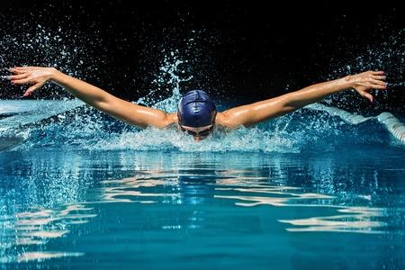 Jonge vrouw in blauwe pet en zwemkleding in het zwembad