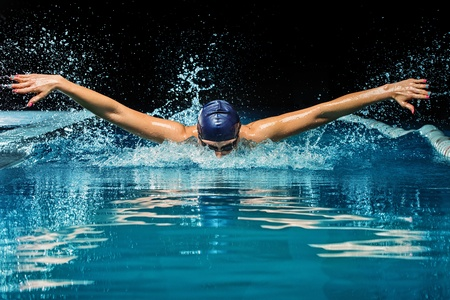 Young woman in blue cap and swimming suit in pool Stok Fotoğraf - 25642529