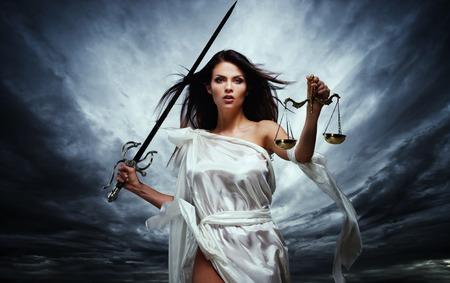 Femida, Godin van Rechtvaardigheid, met schubben en zwaard tegen dramatische stormachtige hemel Stockfoto