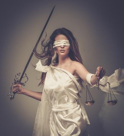 Femida, Godin van Rechtvaardigheid, met schubben en zwaard dragen blinddoek Stockfoto
