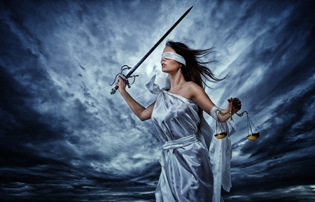 Femida, Goddess of Justice, with scales and sword wearing blindfold against dramatic stormy sky Stock Photo