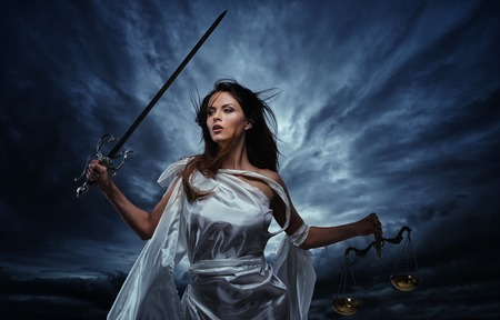 Femida, Goddess of Justice, with scales and sword against dramatic stormy sky Stok Fotoğraf - 25988789