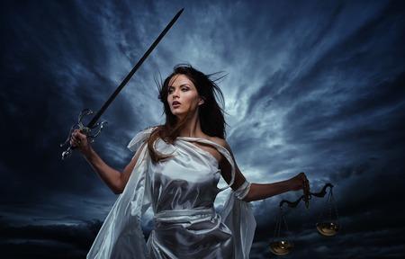 Femida, Godin van Justitie, met schubben en zwaard tegen dramatische stormachtige hemel