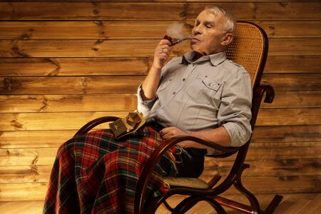 Senior man with smoking pipe sitting on rocking chair in homely wooden interior Imagens
