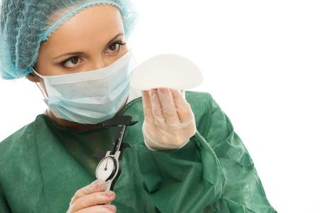 シリコン乳房インプラントとキャリパーのプラスチック外科医女 写真素材