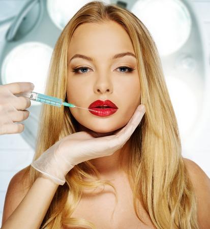 Joven y bella mujer con los labios rojos Botox jeringa Foto de archivo - 26674832