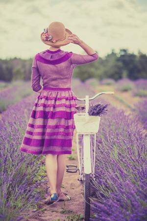 Vrouw in paarse jurk en hoed met retro fiets in lavendel veld Stockfoto