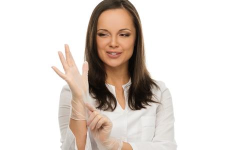 Jonge positieve brunette arts brengen op latex handschoenen