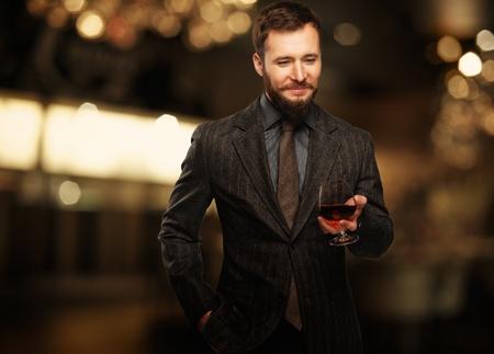 ハンサムな身なりのよいジャケットの男性の飲料のガラス