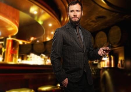 レストランのインテリアの飲料のガラスとジャケットでハンサムな身なりの男