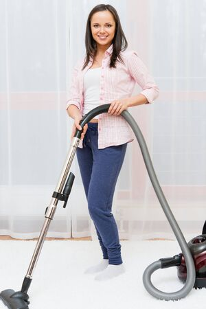 Young cheerful brunette woman vacuum cleaning carpet in home interior