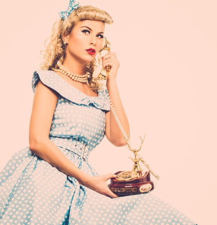 Coquette blond pin up style young woman in blue dress with vintage phone
