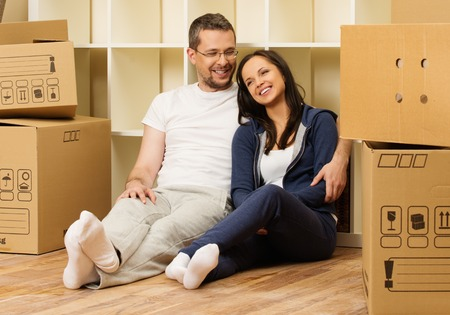 Young positive couple  among boxes in their new home Banco de Imagens