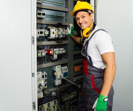 Vrolijke elektricien in een veiligheids-hoed op een fabriek