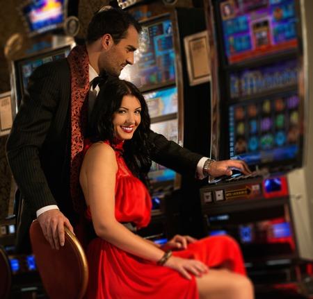 カジノでスロット マシンの近くの美しい若いカップル