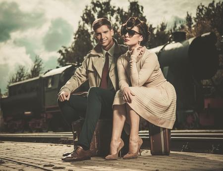 鉄道駅プラットフォームのスーツケースの上に座って美しいビンテージ スタイルのカップル