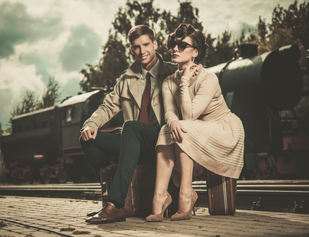 Beautiful vintage style couple sitting on suitcases on  train station platform