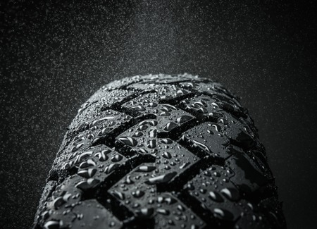 Close-up shot of classical motorcycle tire tread in wet weather condition  Stock Photo