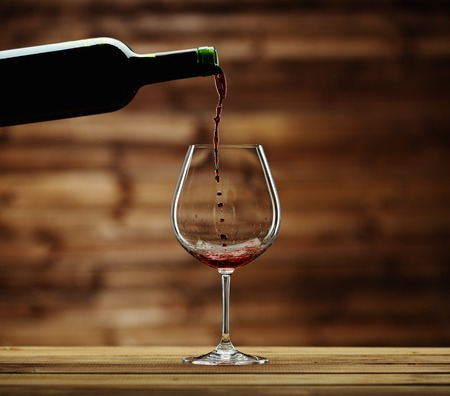 Pouring red wine into the glass against wooden background Stok Fotoğraf - 28177225