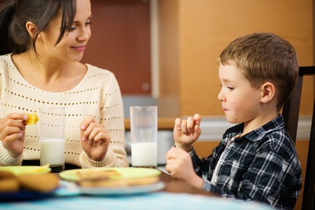 Young happy mother and her child eating healthy breakfast  Stock Photo