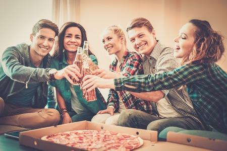 ピザとドリンク インテリアで祝うのボトルと若い多民族友達のグループ