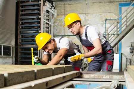 작업자와 공장에서 품질 검사를 수행하는 안전모의 감독 스톡 콘텐츠