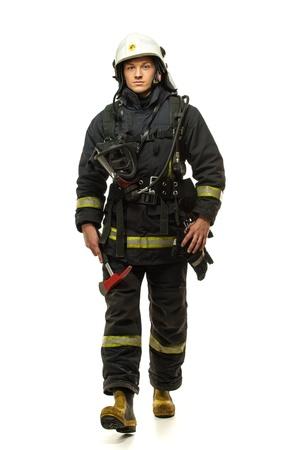 Jonge brandweerman met helm en bijl op wit wordt geïsoleerd