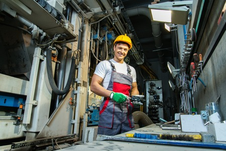Worker in safety hat in machinery room on a factory Imagens