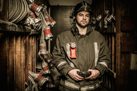 Firefighter in storage room with fire hoses  Stock Photo