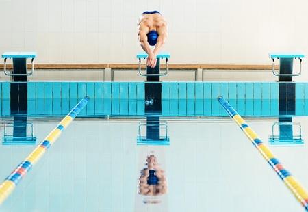 Jonge gespierde zwemmer springen uit startblok in een zwembad