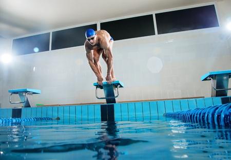 Jonge gespierde zwemmer in lage positie op startblok in een zwembad Stockfoto