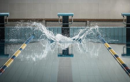 水泳スイミング プールでジャンプ後の飛散 写真素材