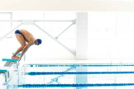 Young muscular swimmer in low position on starting block in a swimming pool Stok Fotoğraf - 28783519