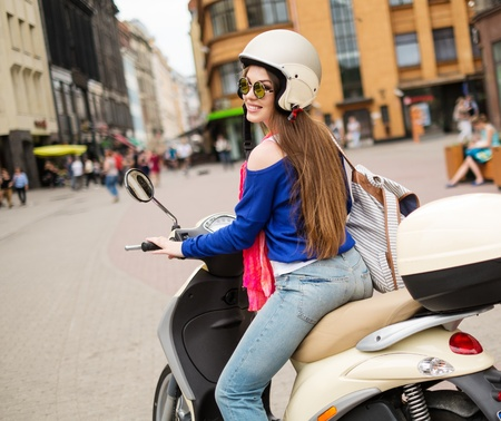 Young cheerful girl driving scooter in in european city  Stock Photo