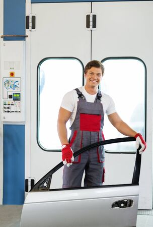 priming paint: Cheerful serviceman with car door near paint booth in a car body workshop Stock Photo
