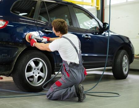 shop skill: Serviceman polishing car body with machine  in a workshop