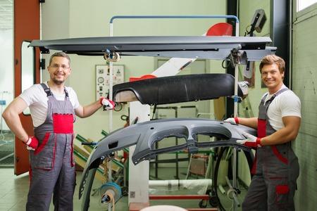 Twee werknemers met auto bodykit klaar voor het schilderen in een workshop