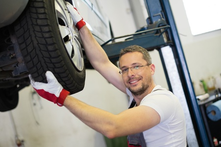 auto lift: Mechanic checking wheel bearings in a car workshop