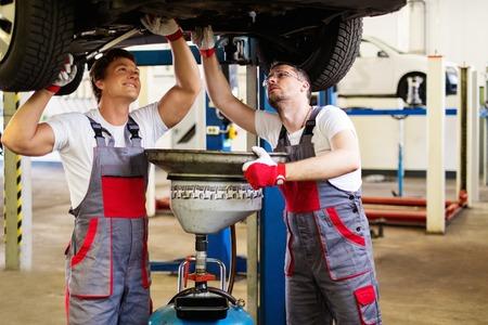 herramientas de mecánica: Dos mecánico de cambiar el aceite en un taller de coches Foto de archivo
